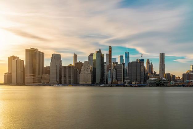 Cityscape van new york met de brug van brooklyn over de rivier van het oosten in de avondtijd, horizon de van de binnenstad van de vs