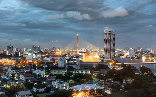 Cityscape van rama 8 brug over de chaophraya-rivier met gebouwen die bij schemer gloeien