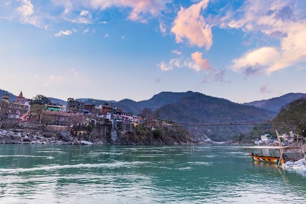 Cityscape van rishikesh bij zonsondergang, heilige stad en reisbestemming in india. kleurrijke lucht en wolken weerspiegelt over de rivier de ganges.