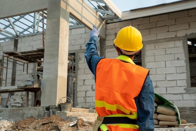 Civiel-ingenieur die veiligheidsharnas en veiligheidslijn draagt die zich bij bouwwerf bevindt, ingenieur die aan bouwterrein werkt.