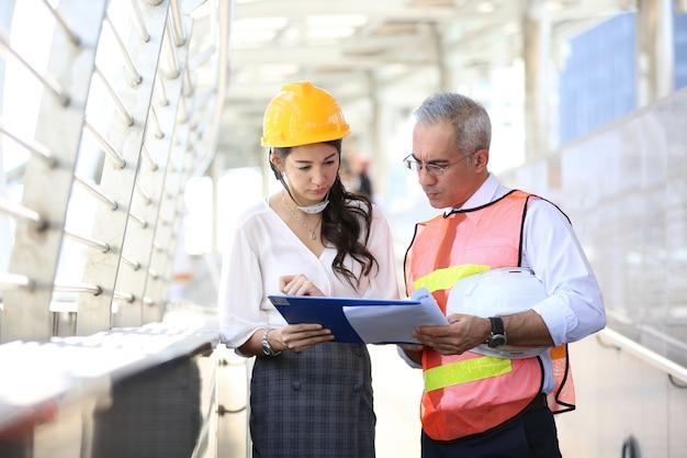 Civiel-ingenieurs die blauwdrukken op een bouwplaats bekijken
