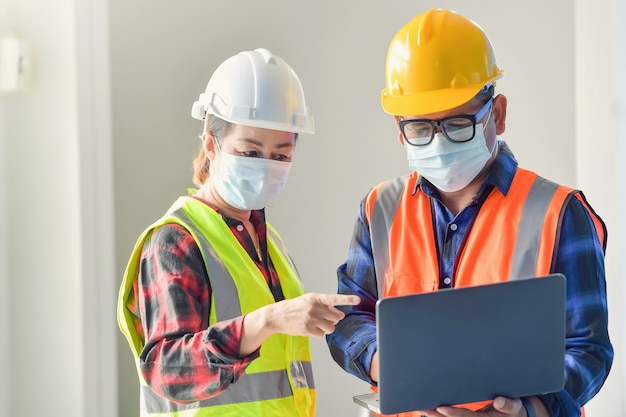 Civiele bouwingenieur die met laptop bij bureaubureau op bouwwerf werkt.