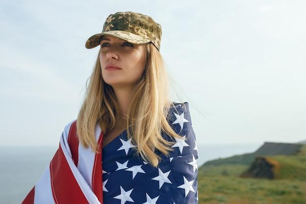 Civiele vrouw in de militaire pet van haar man. een weduwe met een vlag van de verenigde staten vertrok zonder haar man. memorial day voor gesneuvelde soldaten in de oorlog. 27 mei is een herdenkingsdag.