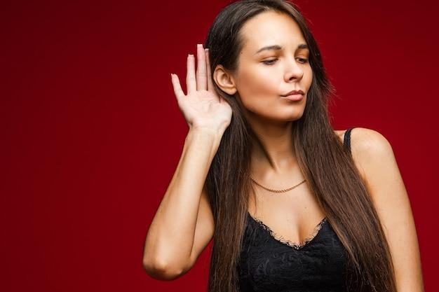 Ckaukasische vrouw met aantrekkelijk uiterlijk luistert naar iemand, foto op rood