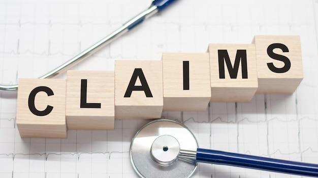 Claims woord geschreven op houten blokken en stethoscoop op licht