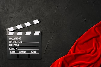 Clapperboard dichtbij rode doek