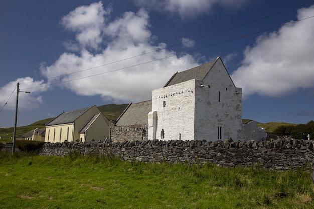 Clare island abbey omgeven door groen onder een blauwe lucht en zonlicht in ierland