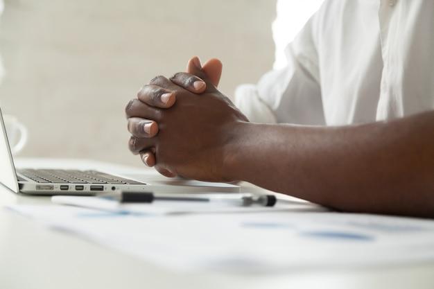 Clasped mannelijke zwarte handen op bureau, sluit omhoog mening