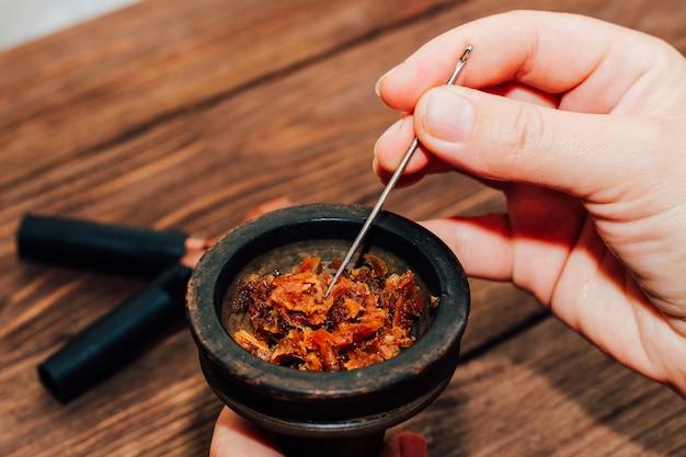 Clay bowl voor waterpijp met kokos kolen, houten mondstukken op een houten achtergrond bovenaanzicht. meisje vult rooktabak.