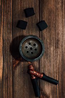 Clay bowl voor waterpijp met kokos kolen, houten mondstukken op een houten achtergrond bovenaanzicht.