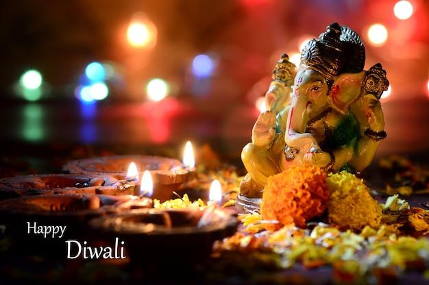 Clay diya-lampen staken samen met lord ganesha aan tijdens diwali-viering