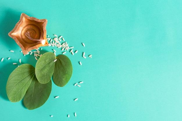 Clay diya-lampen staken tijdens dussehra aan met groen blad en rijst op groen