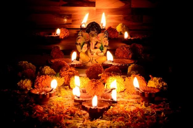 Clay diya-lampen verlicht met lord ganesha tijdens diwali-viering. groeten card design indian hindu light festival genaamd diwali
