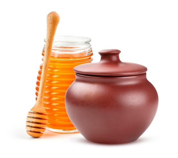 Clay honey-pot en glaskruik op witte achtergrond wordt geïsoleerd die