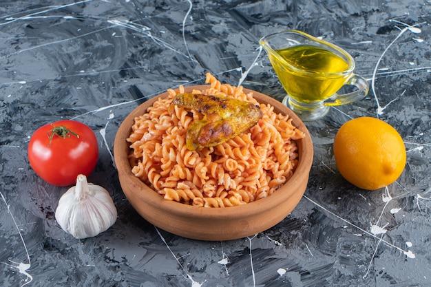 Clay kom heerlijke fusilli pasta met gebakken vleugel op marmeren oppervlak.