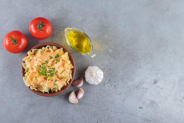 Clay kom heerlijke romige macaroni met olie en groenten op stenen achtergrond.
