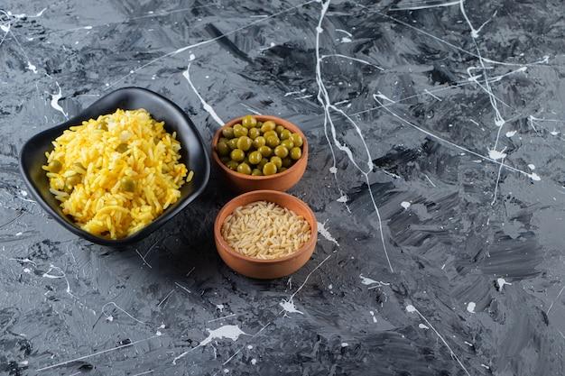 Clay kommen met gekookte rijst en groene erwten op marmeren achtergrond.