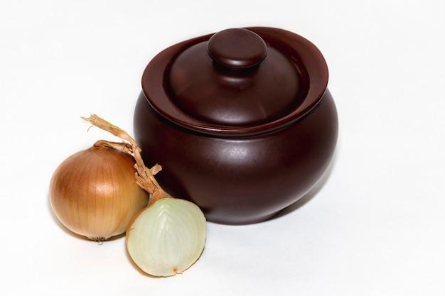 Clay pot op een witte plaat met verse grote uien. rustieke keuken. uien soep.