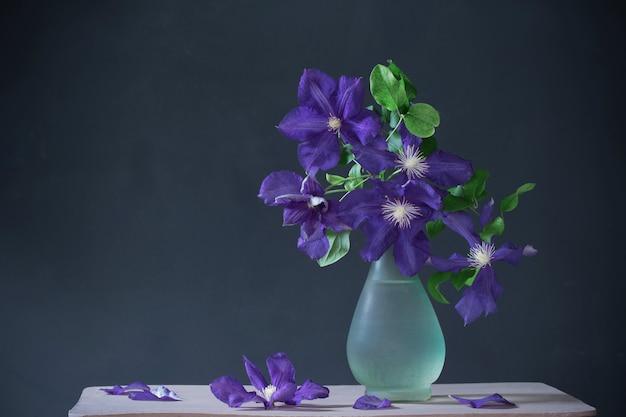 Clematis bloemen in glazen vaas op vintage houten plank