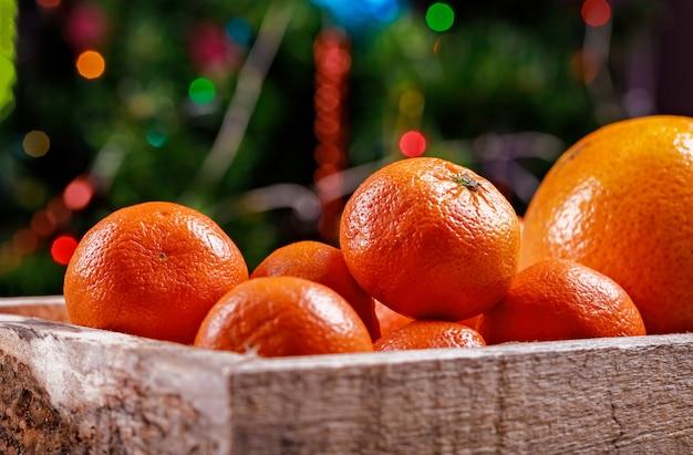 Clementines of mandarijnen in de doos op kerstverlichting.