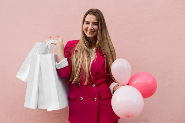 Cliënt die modekleding draagt en ballonnen middelgroot schot houdt