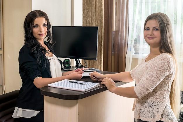 Cliënt geeft haar creditcard aan de beheerder in de schoonheidssalon