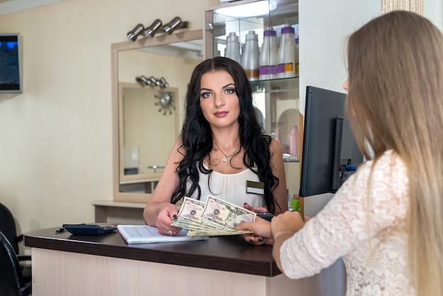 Cliënt in de schoonheidssalon geeft dollars aan receptioniste
