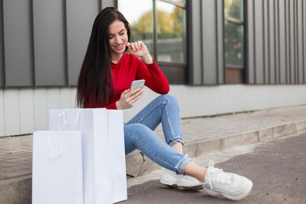 Client in rood shirt zitten en met behulp van haar mobiele telefoon