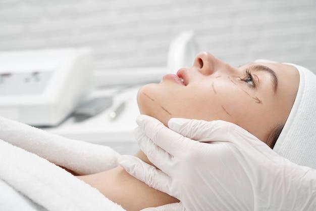 Cliënt met markup op gezicht bezoekende chirurg in kliniek