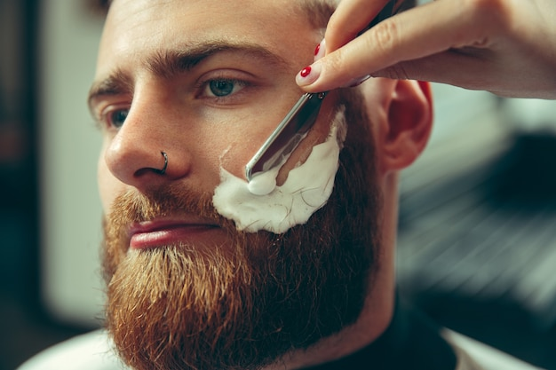 Cliënt tijdens baardscheren in kapperszaak. vrouwelijke kapper bij salon. geslachtsgelijkheid. vrouw in het mannelijke beroep. handen sluiten omhoog