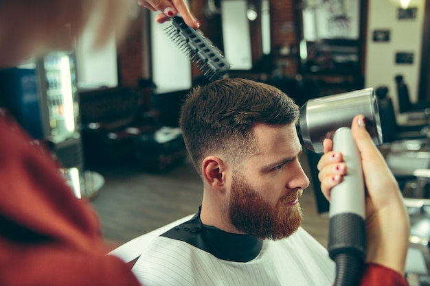 Cliënt tijdens baardscheren in kapperszaak. vrouwelijke kapper bij salon. geslachtsgelijkheid. vrouw in het mannelijke beroep.