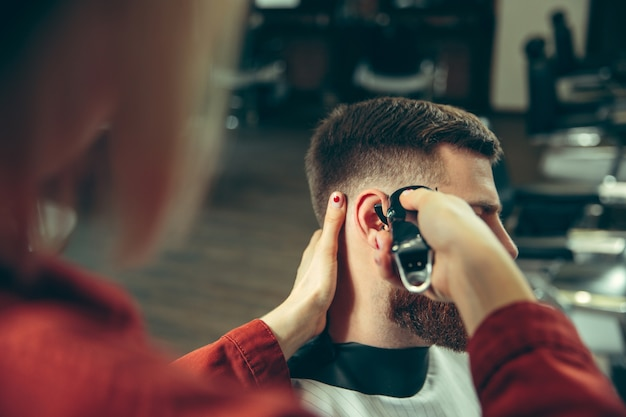 Cliënt tijdens baardscheren in kapperszaak. vrouwelijke kapper bij salon. geslachtsgelijkheid