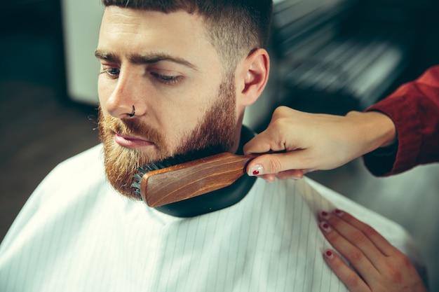 Cliënt tijdens het scheren van de baard in de kapperszaak. vrouwelijke kapper bij salon. geslachtsgelijkheid. vrouw in het mannelijke beroep. handen sluiten omhoog
