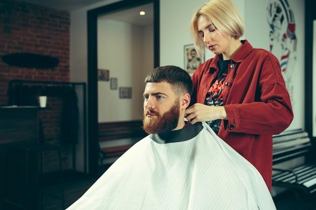 Cliënt tijdens het scheren van de baard in de kapperszaak. vrouwelijke kapper bij salon. geslachtsgelijkheid. vrouw in het mannelijke beroep.