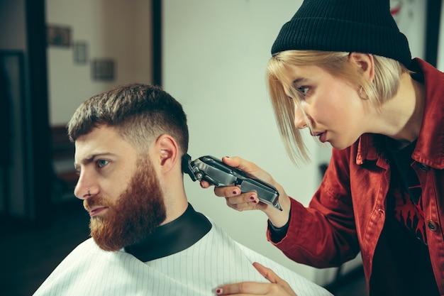 Cliënt tijdens het scheren van de baard in de kapperszaak