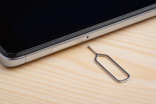 Clip voor het verwijderen van de simkaarthouder in de buurt van moderne mobiele telefoon