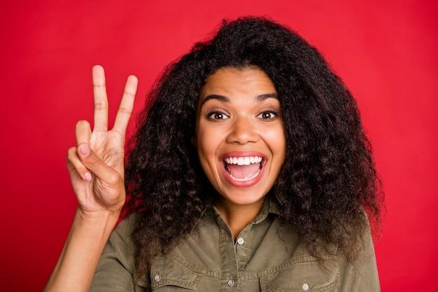 Cloe up portret van vrolijke positieve schattig vrij lief aardig meisje emoties uiten op gezicht tonen v-teken geïsoleerd