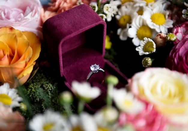 Cloeseup van trouwring in rode doos met bloemen arrangement decoratie