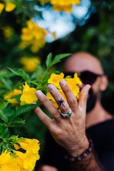 Close shot van brute gebruinde bebaarde man in zonnebril met palmboom tatoeage op vinger stands omgeven door gele bloemen in park