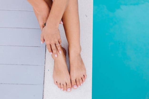 Close shot vrouw voeten en handen. vrouw zit op de rand van het blauwe zwembad op vakantie