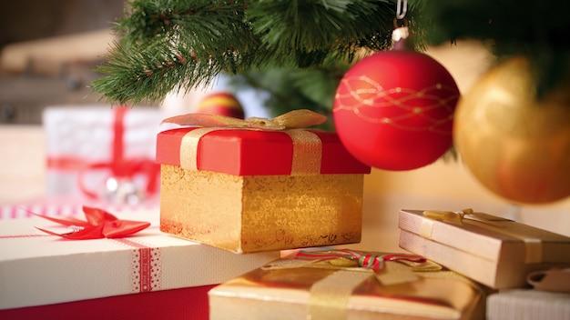 Close-up 4k-beelden van camera die langzaam uitzoomt uit een grote hoop geschenken en cadeautjes die onder de kerstboom in de woonkamer liggen. perfecte foto voor uw wintervakanties en vieringen