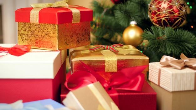 Close-up 4k-beelden van de camera die langzaam naar veel kerstcadeaus en cadeautjes beweegt over lichten en kerstboom. perfecte foto voor uw wintervakanties en vieringen