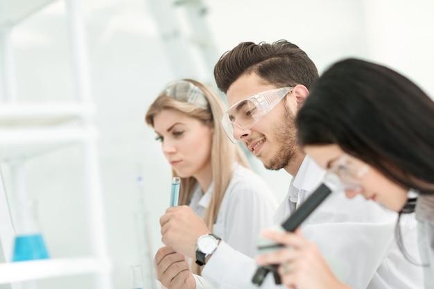 Close-up.a groep jonge wetenschappers voert experimenten uit in het laboratorium. wetenschap en gezondheid