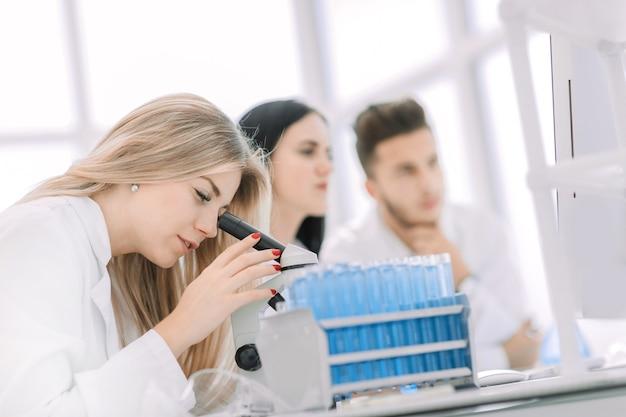 Close up.a moderne vrouwelijke wetenschapper kijkt naar een microscoop in een laboratorium. wetenschap en gezondheid