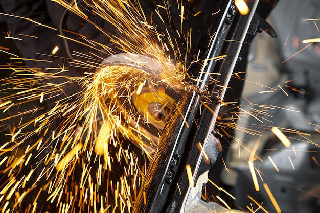 Close-up aan de zijkanten zorgen voor heldere vonken van de haakse slijpmachine. een jonge mannelijke lasser in werkende handschoenen maalt een oude auto met haakse slijper in de garage