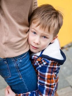 Close-up aanbiddelijke jonge jongen die zijn moeder houdt