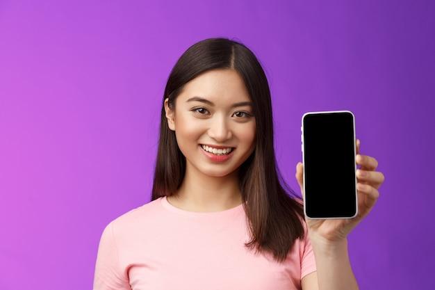 Close-up aantrekkelijke, aangename vrouwelijke winkelbediende presenteert nieuwe telefoon-app, houdt smartphone-telefoonscherm vast, introduceert applicatie op display, staat opgetogen paarse achtergrond.