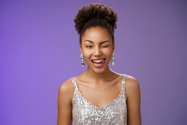 Close-up aantrekkelijke afro-amerikaanse vrouw in zilveren trendy avondjurk oorbellen knipogen gelukkig tonen tong brutaal graag genieten van geweldige disco party dansen gek rond veel plezier.