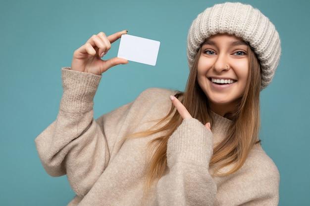 Close-up aantrekkelijke sexy positieve glimlachende jonge donkere blonde vrouw die beige sweater draagt en