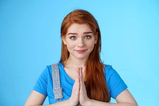 Close-up aantrekkelijke tedere roodharige vrouw die mooi alsjeblieft vraagt, smeekt, handen vasthoudt bid, namaste gebaar, kijk oprecht medelijden, glimlachend smekend om hulp, sta op blauwe achtergrond